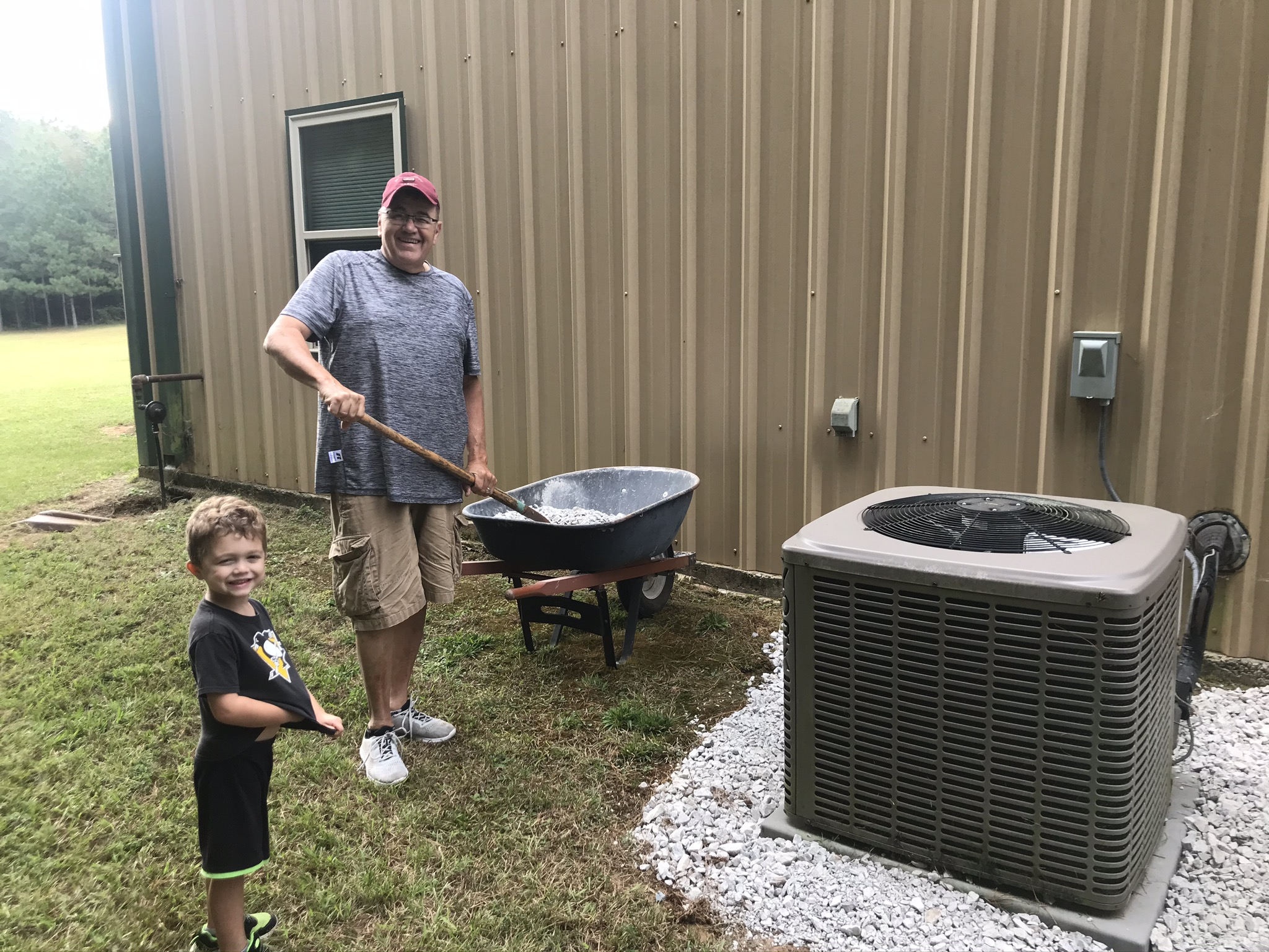"Keith ""Pap"" Graybill and grandson Ian spreading gravel"